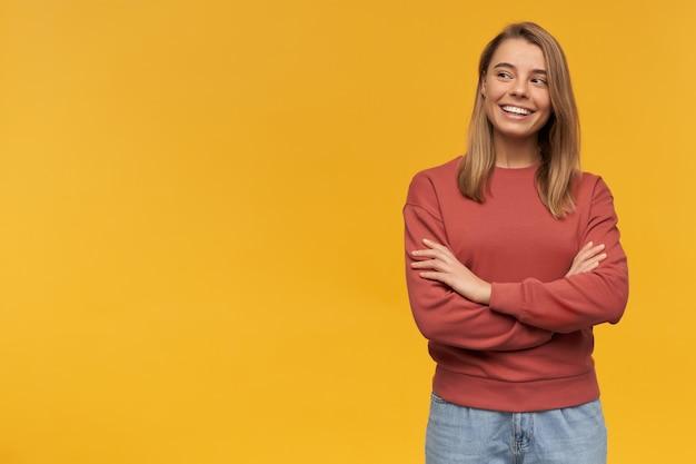 Wesoła piękna młoda kobieta w bluzie z terakoty, patrząc z boku i stojąca z rękami skrzyżowanymi na żółtej ścianie