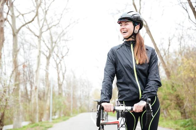 Wesoła piękna młoda kobieta w kasku ochronnym z rowerem spacerowym w parku