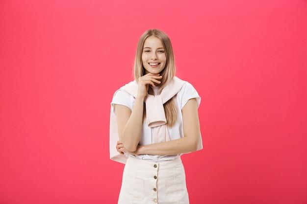 Wesoła piękna młoda kobieta w różowym swetrze