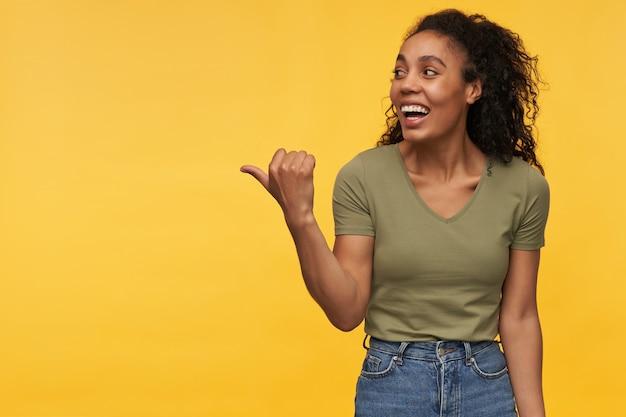 Wesoła piękna młoda kobieta w zwykłych ubraniach patrząca i wskazująca na bok na copyspace odizolowanej nad żółtą ścianą