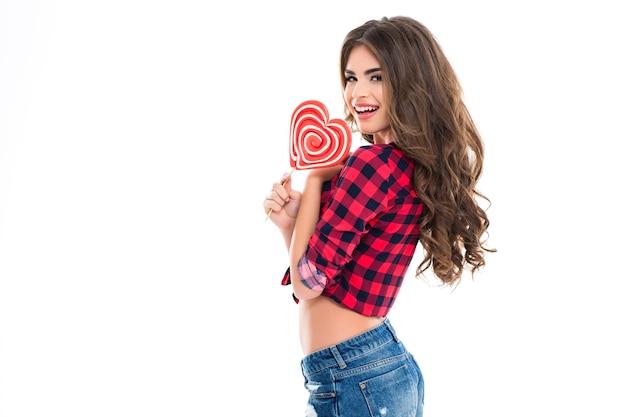 Wesoła piękna młoda kobieta z długimi kręconymi włosami trzymająca cukierki w kształcie serca i uśmiechająca się nad białą ścianą