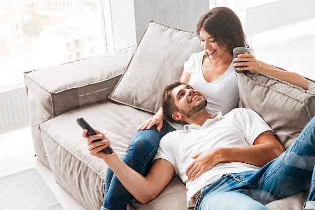 Wesoła piękna młoda para pije kawę i ogląda telewizję w domu