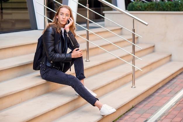 Wesoła piękna studentka mówi na smartfonie przy schodach na ulicy, ciesząc się spacer na świeżym powietrzu.