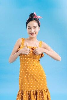 Wesoła podekscytowana dziewczyna pinup pokazująca kciuk w górę na niebiesko