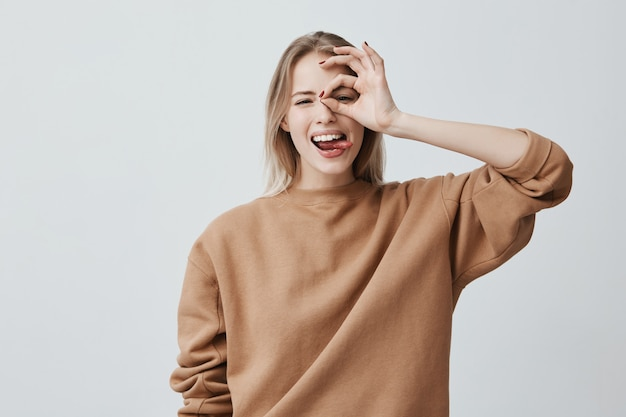 Wesoła podekscytowana kobieta z długimi prostymi włosami o blond włosach, pokazująca ok obiema rękami, udająca, że nosi okulary i szeroko uśmiechająca się, ciesząca się swoim beztroskim szczęśliwym życiem
