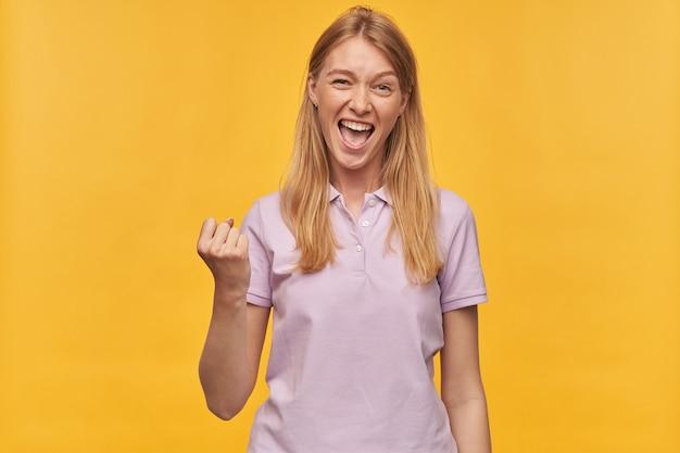 Wesoła podekscytowana kobieta z piegami w lawendowej koszulce krzyczy i pokazuje gest zwycięzcy na żółto