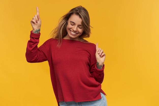Wesoła podekscytowana młoda kobieta w bluzie z terakoty tańczy i wskazuje na żółtą ścianę. wygląda na szczęśliwego