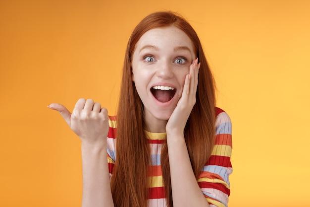 Wesoła podekscytowana pod wrażeniem gadatliwa dziewczyna wskazująca zdziwiony kciuk w lewo opadająca szczęka uśmiechnięta szeroko dotyk policzek zachwycona, ciekawe wydarzenie dyskutuje o niesamowitym cudownym wykonaniu, pomarańczowe tło.