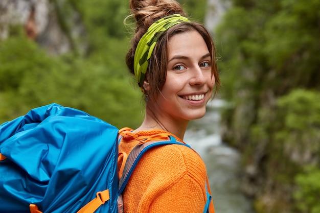Wesoła podróżniczka wybiera się na wycieczkę, nosi plecak, stoi nad strumieniem, szeroko się uśmiecha