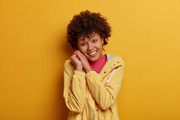 Wesoła pozytywna afroamerykanka uśmiecha się delikatnie, opiera głowę na dłoniach, zadowolona z komplementu, ubrana w kurtkę, obserwuje coś przyjemnego, pozostaje na jasnej stronie wyraża entuzjazm i pozytywne nastawienie