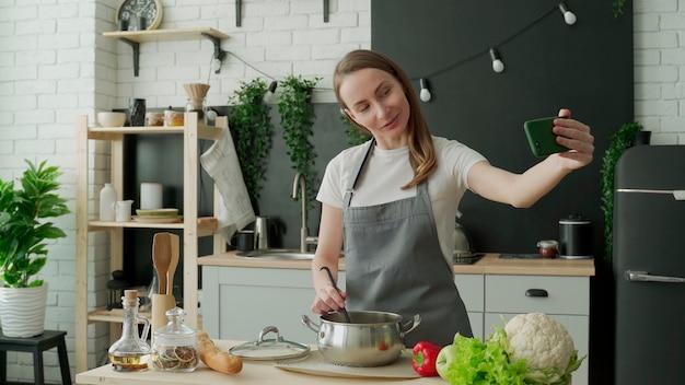 Wesoła, pozytywna blogerka w fartuchu nagrywa na swoim telefonie komórkowym blog o gotowaniu