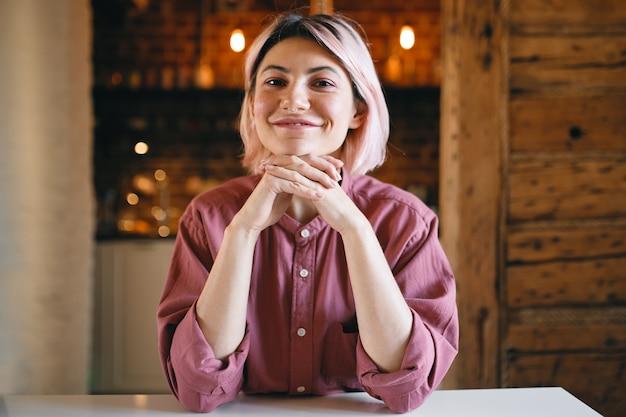 Wesoła, pozytywna młoda kobieta z różowawymi włosami siedzi w domu na złotym jasnym tle z optymistycznym radosnym wyrazem twarzy, trzymając ręce pod brodą i szeroko uśmiechając się do kamery