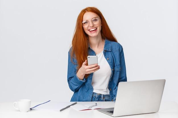 Wesoła, przyjazna, charyzmatyczna rudowłosa projektantka, freelancer z rudymi włosami, okularami, śmiechem beztroskim, trzymaniem smartfona, pracą nad projektem z laptopem, piciem kawy