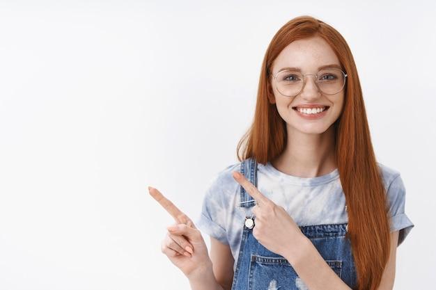 Wesoła przyjazna szczera rudowłosa dziewczyna z niebieskimi oczami, piegami, długimi rudymi włosami skierowanymi w lewo, uśmiechnięta uprzejma i towarzyska wprowadza promo, stoisko biała ściana rozbawiona radosna, szczęśliwa pomoc