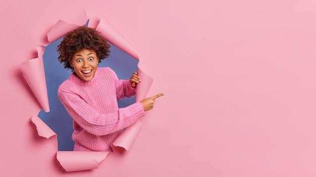 Wesoła, radosna ciemnoskóra kobieta wygląda z radosnym zaskoczeniem i wskazuje po prawej stronie miejsce na kopię dla twoich treści promocyjnych