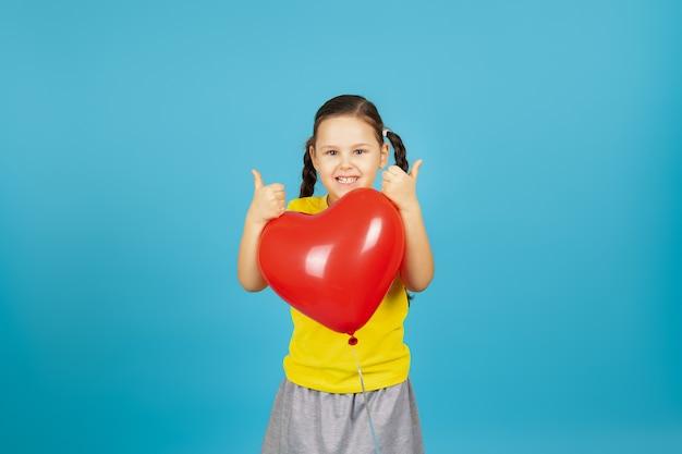 Wesoła, radosna dziewczyna w żółtym t-shircie z kucykiem ściska czerwony balon w kształcie serca i wystawia kciuki do góry