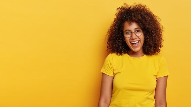 Wesoła, radosna, kręcona, urocza dziewczyna śmieje się ze szczęścia, raduje się z przyjemnych chwil w życiu, ma atrakcyjny wygląd, nosi duże przezroczyste okulary i swobodną żółtą koszulkę, czuje się radośnie