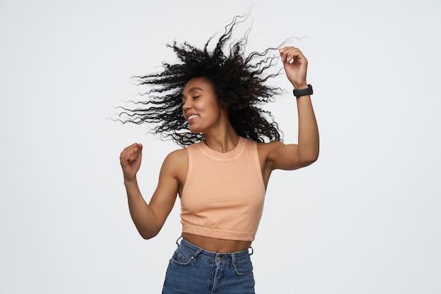 Wesoła, radosna młoda kobieta z zamkniętymi oczami i latającymi kręconymi włosami, tańcząca i mająca imprezę odizolowaną od szarej ściany