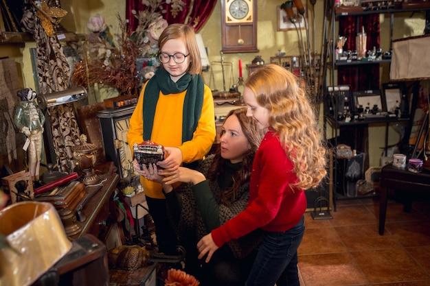 Wesoła rodzina, mama i dzieci szukające dekoracji domu i świątecznych prezentów w sklepie agd