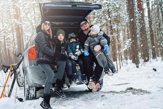 Wesoła rodzina ojca i matki z dziećmi na wakacjach samochodem w zimowym drewnie.