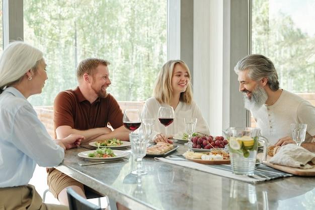 Wesoła rodzina siedzi przy jednym stole w wiejskim domu i rozmawia podczas kolacji