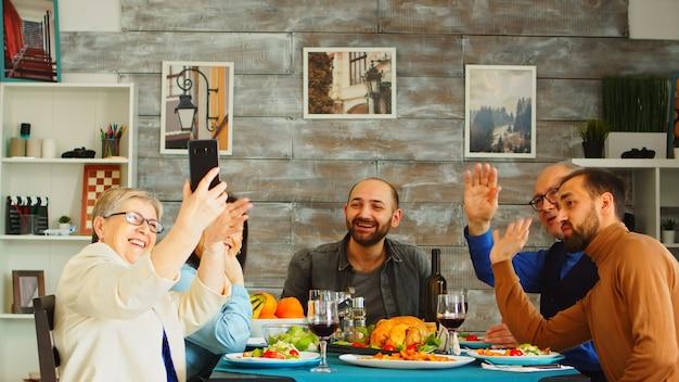 Wesoła rodzina śmiejąca się podczas rozmowy wideo na czacie z telefonu przy kolacji.