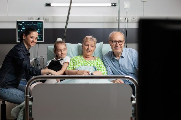 Wesoła rodzina spędza czas z chorą babcią oglądając film w telewizji