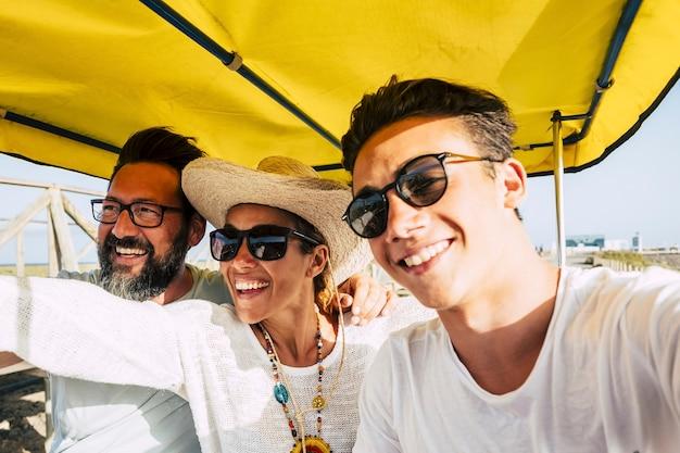 Wesoła rodzina uśmiecha się i śmieje się razem podczas wypoczynku na świeżym powietrzu w słoneczny dzień - koncepcja wakacji i szczęśliwego stylu życia - różne grupy wiekowe i pokolenia bawią się jak przyjaciele