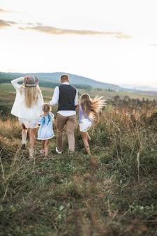 Wesoła rodzina w modnych modnych ubraniach, rodzice i dzieci, cieszący się i biegający razem w górach