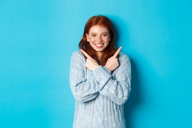 Wesoła ruda dziewczyna pokazuje dwie możliwości, wskazując w bok i uśmiechając się na niebieskim tle