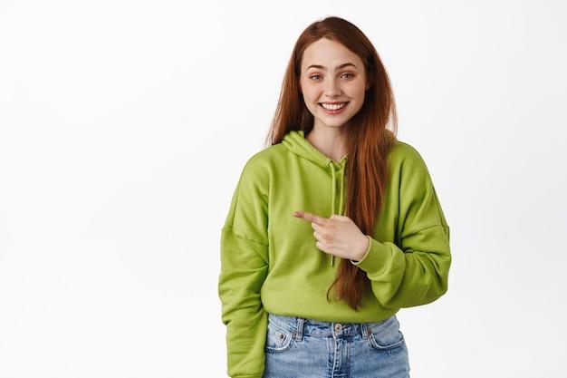 Wesoła ruda dziewczyna wskazująca palcem w lewo i uśmiechająca się białe zęby stojące na białym