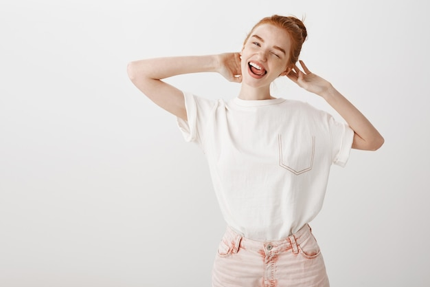 Wesoła ruda dziewczyna wyglądająca beztrosko, uśmiechnięta i mrugająca szczęśliwa