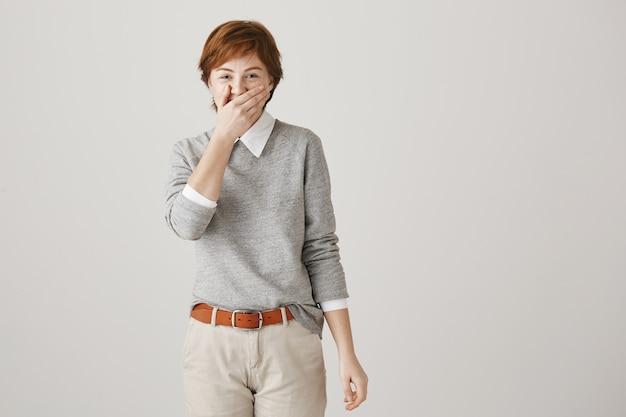 Wesoła ruda dziewczyna z krótką fryzurą, pozowanie na białej ścianie