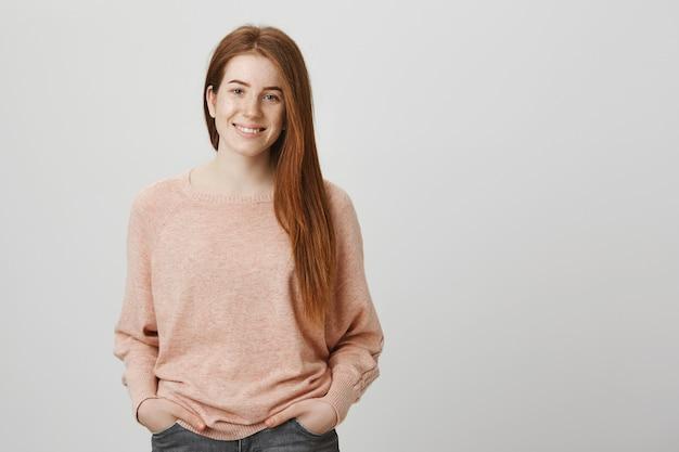 Wesoła ruda dziewczyna z piegami, uśmiechając się