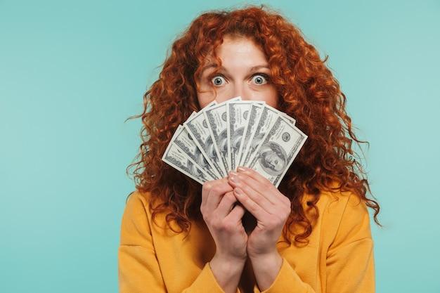 Wesoła ruda kobieta w wieku 20 lat uśmiechnięta i trzymająca garść pieniędzy odizolowanych nad niebieską ścianą