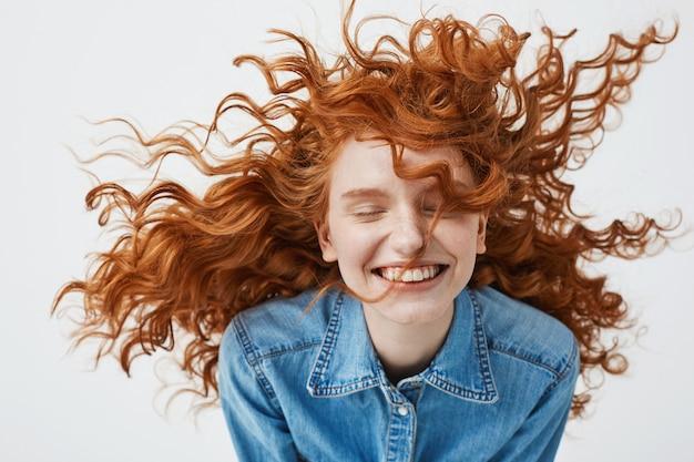 Wesoła ruda kobieta z latającymi kręconymi włosami, uśmiechając się, śmiejąc się z zamkniętymi oczami.