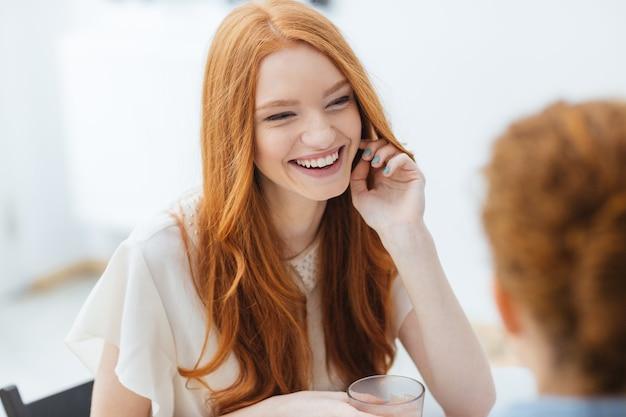 Wesoła ruda ładna młoda kobieta siedzi i śmieje się z przyjacielem w kawiarni
