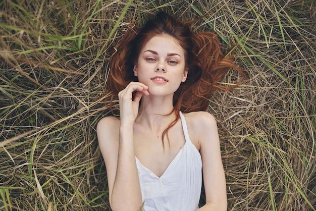 Wesoła rudowłosa kobieta w białej sukni leży na trawie odpoczywa na świeżym powietrzu