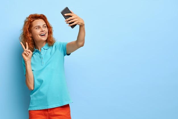 Wesoła rudowłosa kobieta z kręconymi włosami, robi gest pokoju, robi selfie na smartfonie, bawi się telefonem komórkowym, nosi koszulkę