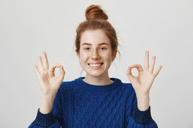 Wesoła rudowłosa uśmiechnięta dziewczyna, pokazująca ok z aprobatą, zapewnia wszystko dobrze
