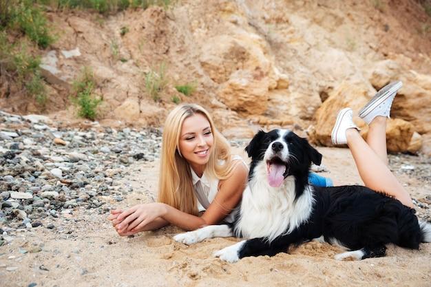 Wesoła śliczna dziewczyna leżąca i relaksująca się z psem na plaży