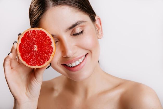 Wesoła śliczna dziewczyna uśmiechnięta, pozowanie z czerwonych zdrowych owoców cytrusowych na białej ścianie.