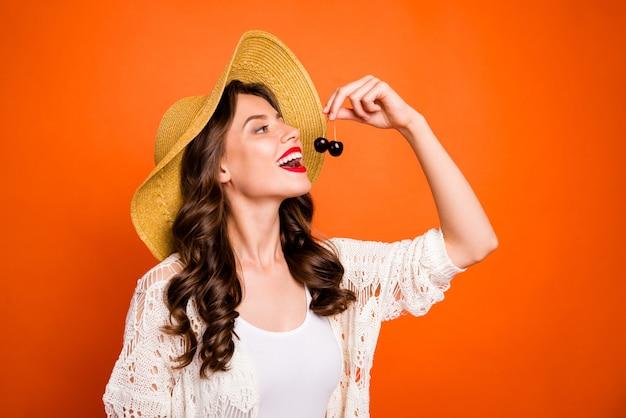 Wesoła śliczna ładna ładna śliczna kobieta gotowa do zjedzenia dwóch wiśni z ustami pomadowanymi na czerwono.