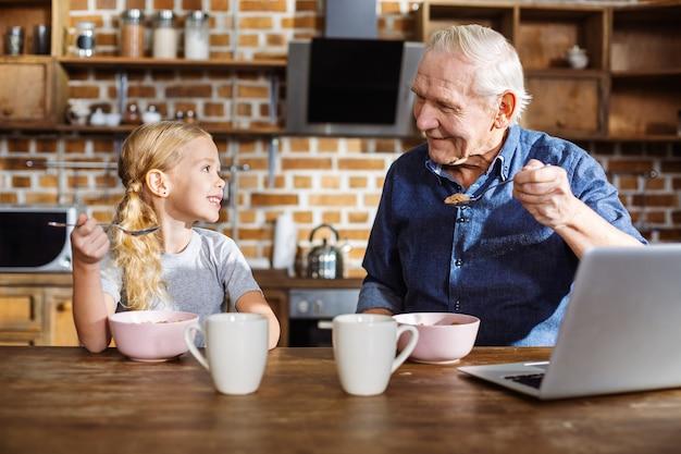 Wesoła śliczna mała dziewczynka je zboża, ciesząc się wczesnym śniadaniem ze swoim ojcem-absolwentem