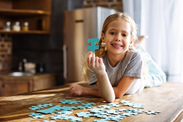 Wesoła śliczna mała dziewczynka leży na stole podczas gry z puzzli