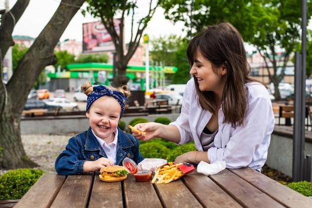 Wesoła śliczna mała dziewczynka siedzi z matką z burgerem i frytkami na stole w kawiarni