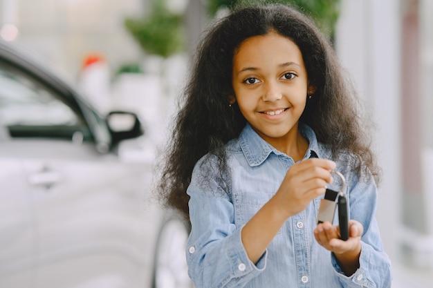Wesoła, śliczna mała dziewczynka szuka, trzyma kluczyki do samochodu, pokazuje to, uśmiecha się i pozuje.