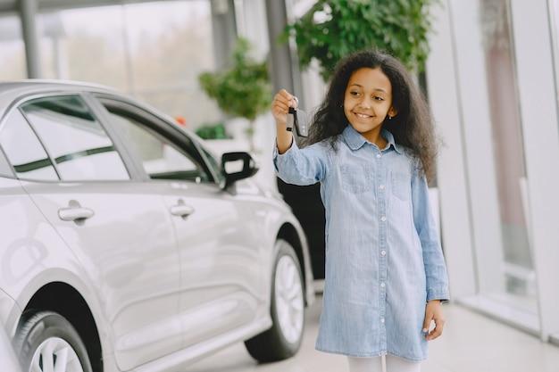 Wesoła, śliczna mała dziewczynka trzyma kluczyki do samochodu, pokazuje to, uśmiecha się i pozuje.