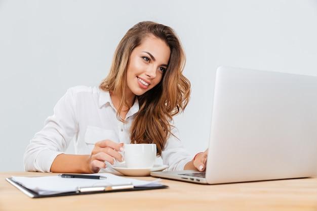 Wesoła śliczna młoda bizneswoman z filiżanką kawy siedzącą i używającą laptopa na białym tle