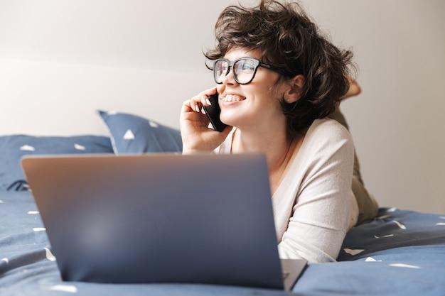 Wesoła śliczna młoda kobieta leży w pomieszczeniu na łóżku przy użyciu komputera przenośnego rozmawiając przez telefon komórkowy.